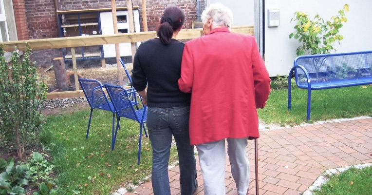 Vårdbiträde går på promenad med patient med demenssjukdom.