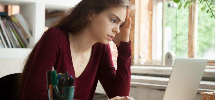 Stressad kvinna sitter vid sin laptop