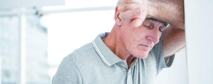 Trött äldre man med KOL lutar sig