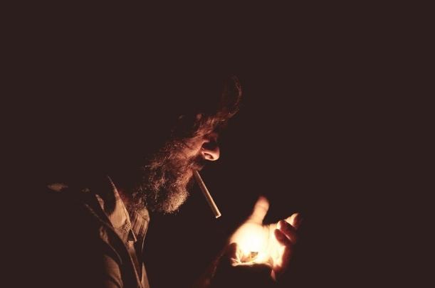 Man som tänder en cigarett.