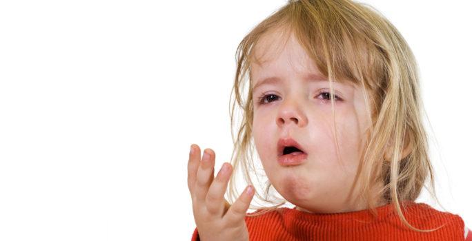 Flicka med lunginflammation hostar