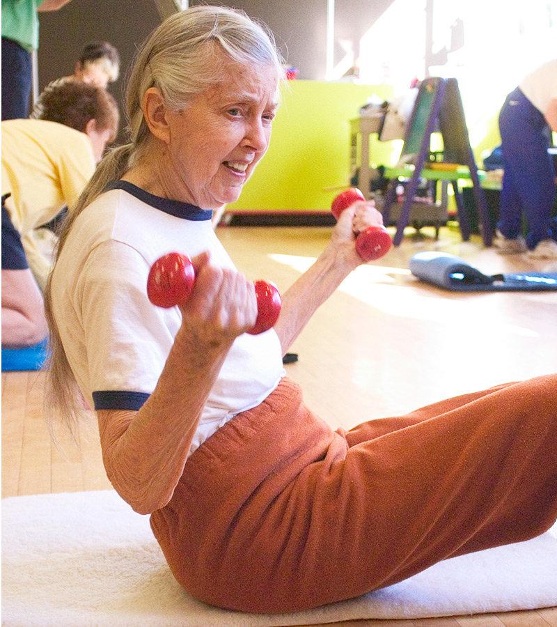 Äldre dam styrketränar med hantlar