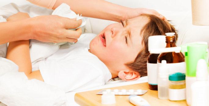 Barn med feber vilar i sängen bredvid febernedsättande läkemedel.
