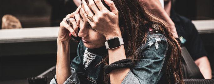 Kvinna med förkylning jobbar och ringer samtal på mobilen.