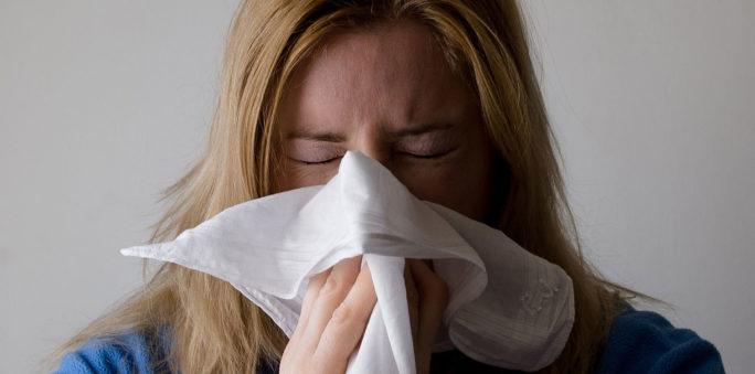 Kvinna med symptom på långvarig förkylning snyter sig i näsduk.