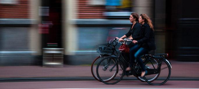 Två kvinnor cyklar till jobbet, ett bra sätt att undvika förkylning.