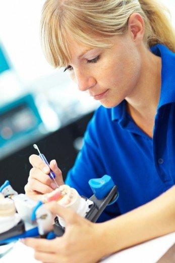Odontolog tillverkar en tandprotes.