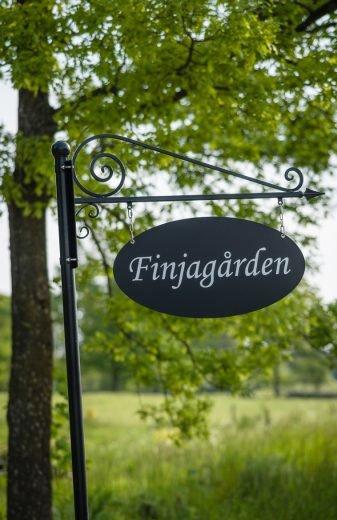 Gammeldags skylt där det står Finjagården.