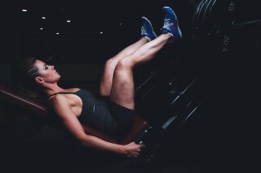 En kvinna tränar knäböj med en maskin.