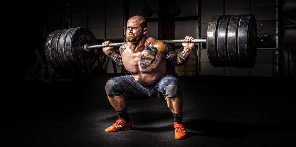 En man gör knäböj med tunga vikter på axlarna