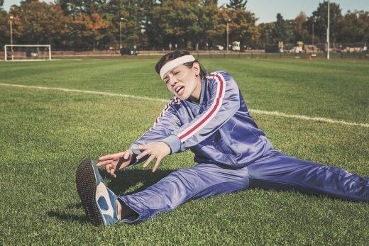 En kvinna stretchar på en fotbollsplan.