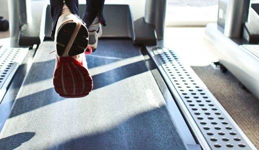 Fötter springer på ett löpband.