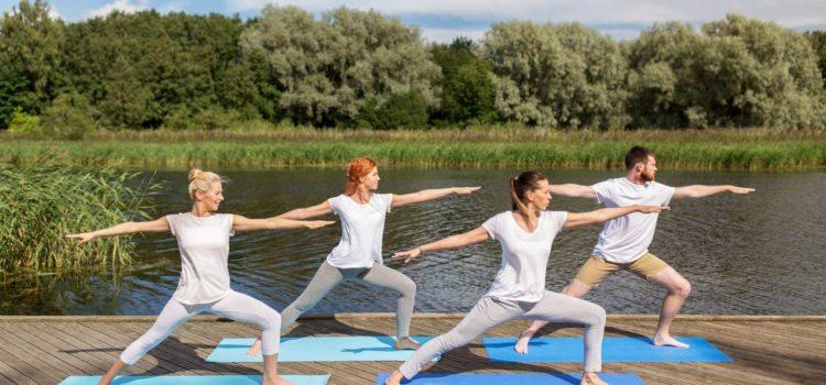 Fyra personer utövar yoga på en strandbrygga