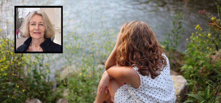 Flicka sitter vid en bäck