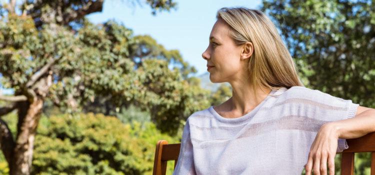 Kvinna sitter på en parkbänk och slappnar av