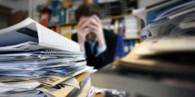 Stressad man på kontoret med hög av dokument och pärmar på bordet.