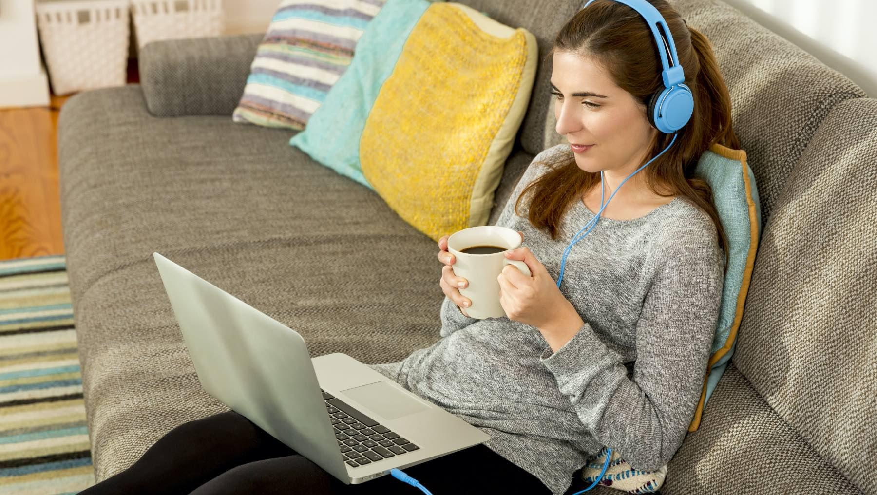 Kvinna sitter på en soffa med sin dator och en kopp kaffe