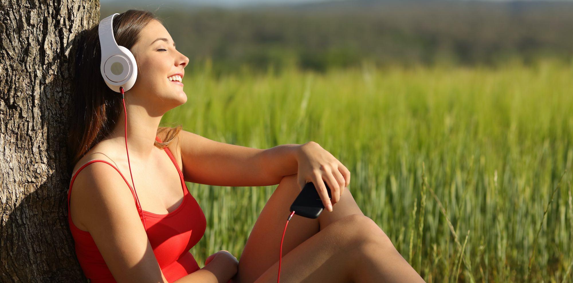 Kvinna sitter under ett träd och lyssnar på musik