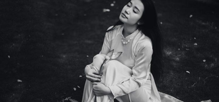 Kvinna med slutna ögon sitter på marken