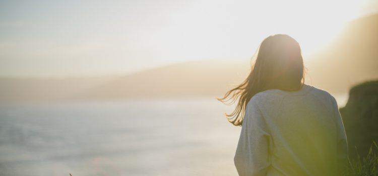 Kvinna sitter vid havet och tittar ut