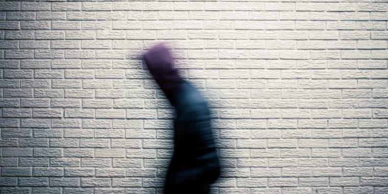 Suddig man går förbi en vit tegelvägg