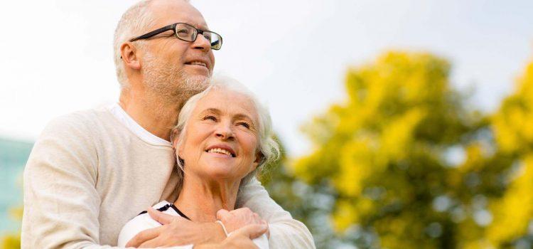 Äldre man ger sin fru en kram bakifrån