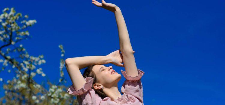 Kvinna sträcker sig mot himlen