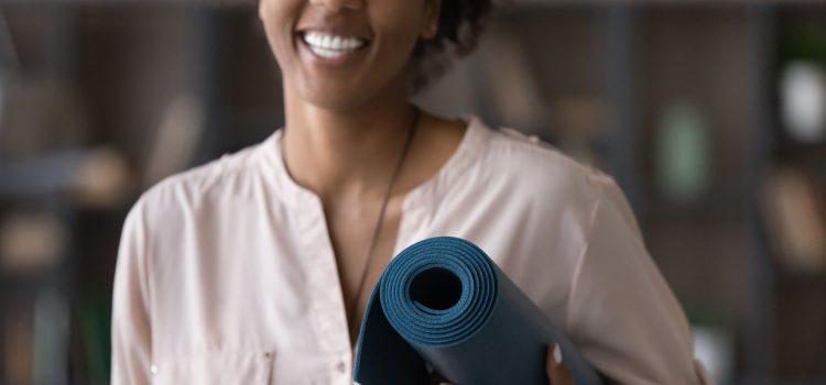 Leende kvinna med yogamatta