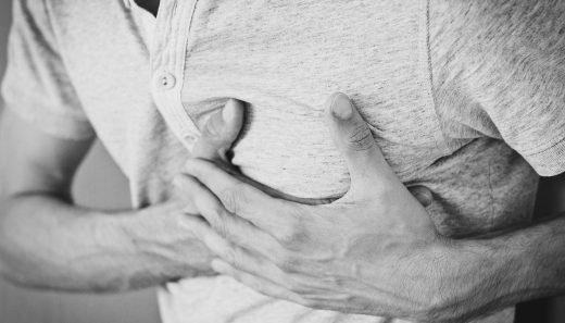En man har bröstsmärtor och håller två händer över hjärtat.