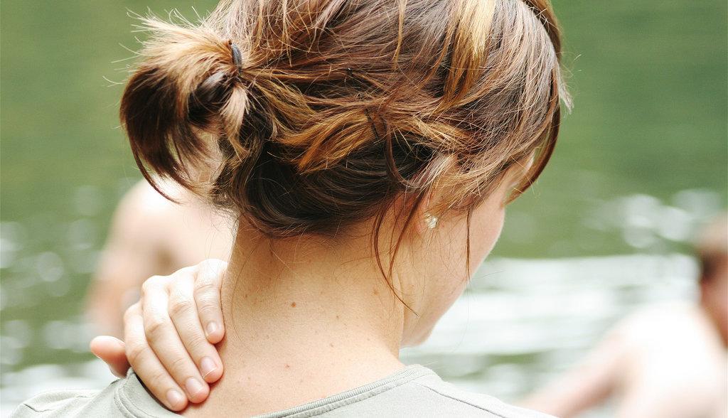 Kvinna som masserar sin nacke på grund av smärta och nackrelaterad yrsel.
