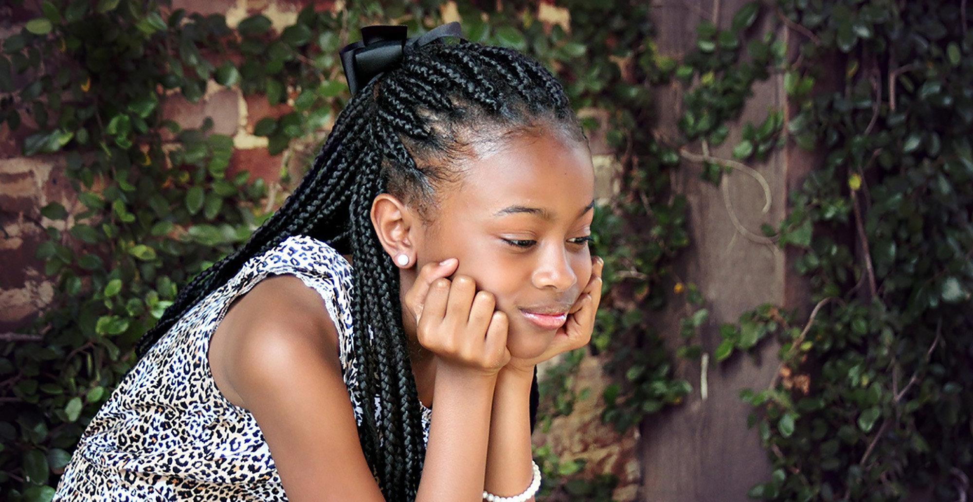 Tjej med IBS-mage som sitter hukad på en bänk och ler. Internet-KBT kan hjälpa ungdomar att må bättre.