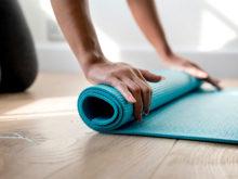 kvinna-rullar-upp-yoga-matta-efter-traningspass