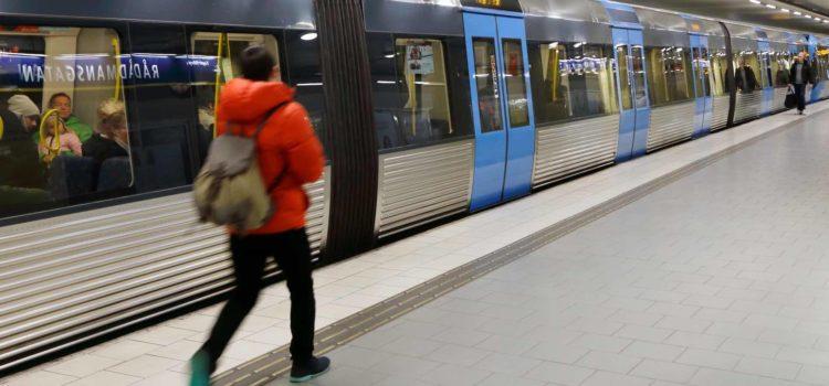 Tunnelbanetåg med stängda dörrar och passagerar på plattformen, vid station Rådmansgatan i Stockholm, Sverige.