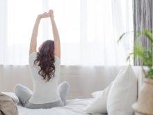 Kvinna stretchar på sin säng