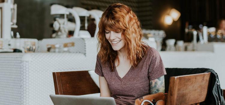 Leende kvinna sitter med sin dator i ett café
