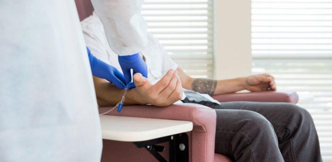 Patient i stol får cytostatika mot cancer genom nål i armen.