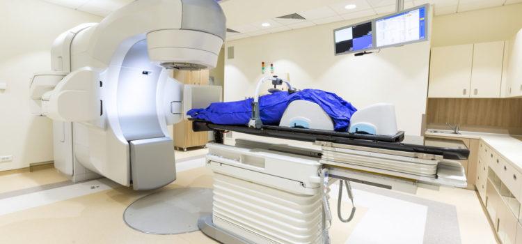 Strålning för behandling av cancer sker på en brits med maskin som ger strålning.
