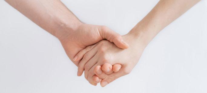 Två personer ger stöd åt varandra vid cancerbesked genom att hålla i händer.
