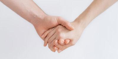 Tvä händer som håller i varandra och ger stöd