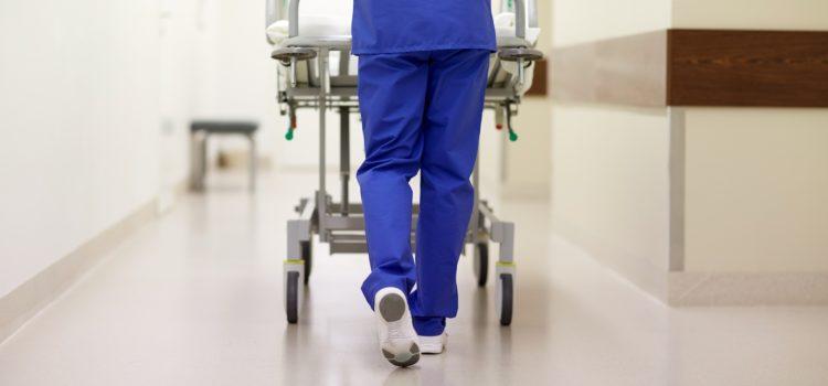 Läkare puttar på en sjukhussäng med en patient med coronavirus