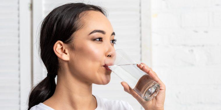 Kvinna dricker vatten för sin muntorrhet