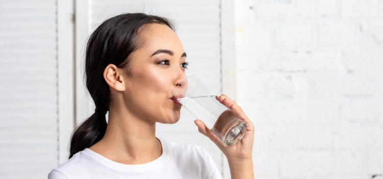 Kvinna lider av muntorrhet dricker vatten