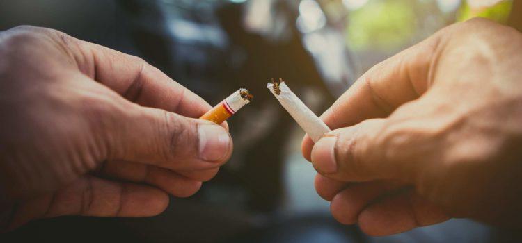 Ett par händer bryter isär en cigarett
