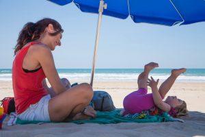Mor och dotter på stranden skyddar sig mot malignt melanom med en parasol.