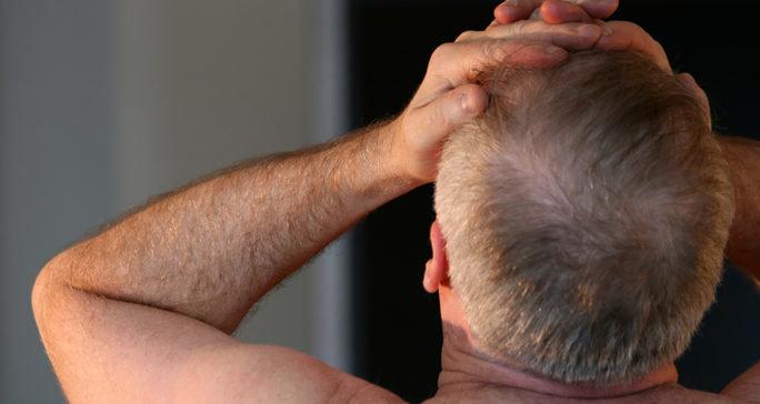 Man som tar sig över huvudet på grund av huvudvärk och trötthet. Vanliga symptom vid järnbrist.