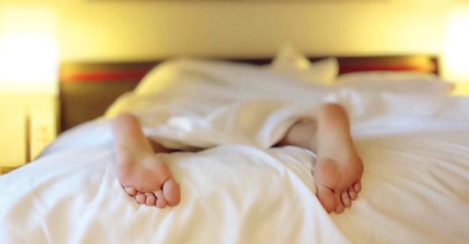 Kvinna som ligger i sängen och sover på grund av järnbrist, ett vanligt symptom som drabbar många.
