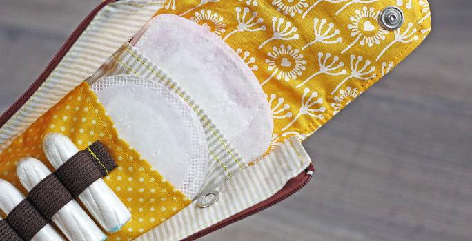 Ett paket innehållande mensskydd som bindor, tamponger och menskoppar.