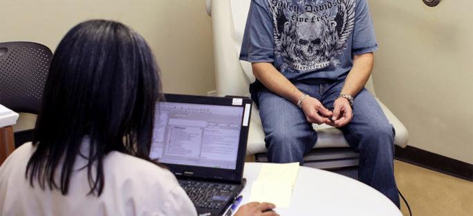 Man som besöker läkare för att få hjälp med en astmautredning.