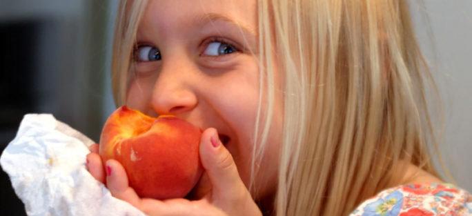 Barn som är allergisk mot kärnfrukt äter en persika.