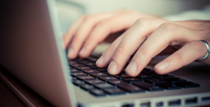 Närbild på en laptop och fingrar som knappar på tangentbord